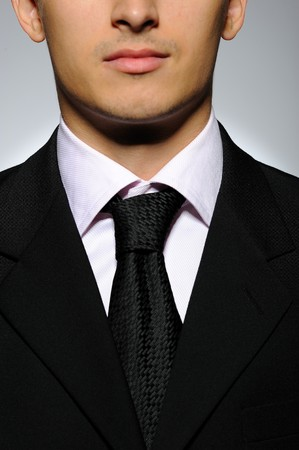 part of Portrait of succesful  business man in formal suit and black tie. gray background photo