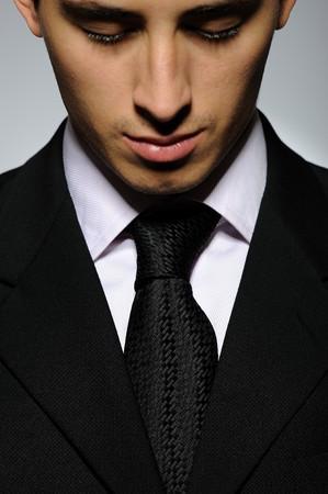 lazo negro: Retrato de hombre de negocios exitoso en traje formal y corbata negra mirando hacia abajo. fondo gris