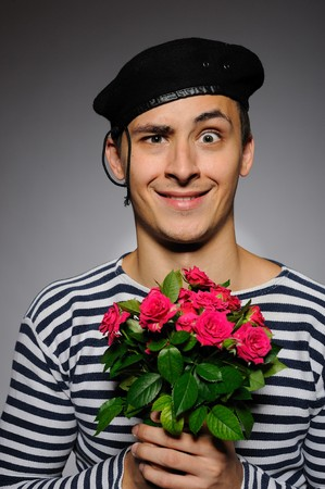 Funny emotional romantic sailor man holding rose flowers prepared for a date photo