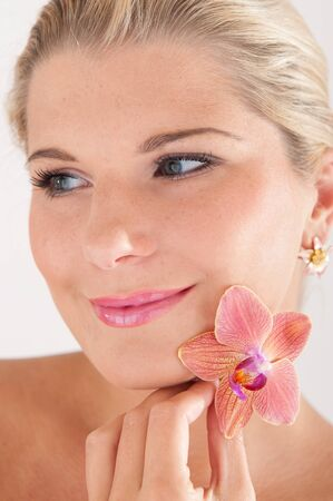 beautiful woman with healthy skin and orchid flower Stock Photo