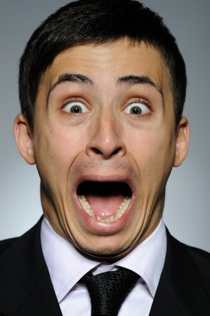 Portrait of stressed  business man in formal suit and black tie screaming.  gray background photo
