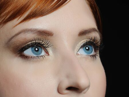 Beautiful macro shot of blue eyes with long lashes and make-up in brown tones