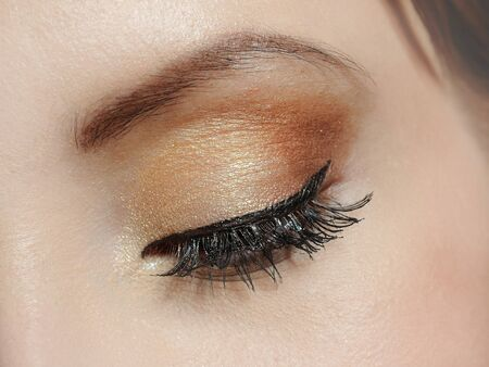 Beautiful macro shot of eye with long lashes and make-up in brown tones