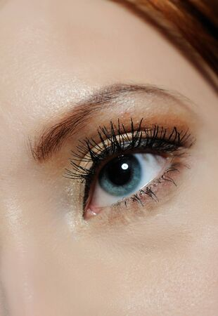 Beautiful macro shot of blue eye with long lashes and make-up in brown tones photo