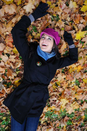 Pretty autumn girl relaxing outdoors in the forest on the fallen leafs photo