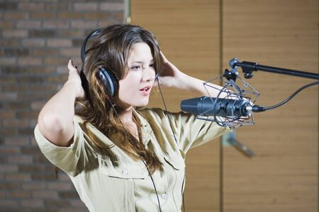 Young beautiful retro woman recording the sound in professional studio with mic and phones. indoor photo