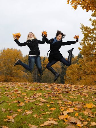 two beautiful girl friends with autumn leafs in a park jumping photo