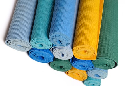 many colorfull yoga mats as a background. isolated on white background photo
