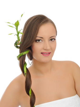 Beautiful spa woman with long healthy hair and pure skin with a bamboo. isolated on white background photo