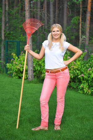 young pretty gardening woman with tools and rakes outdoors  photo