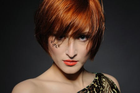 Beautiful red heaired woman portrait with fashion hairstyle and creative trendy make-up photo