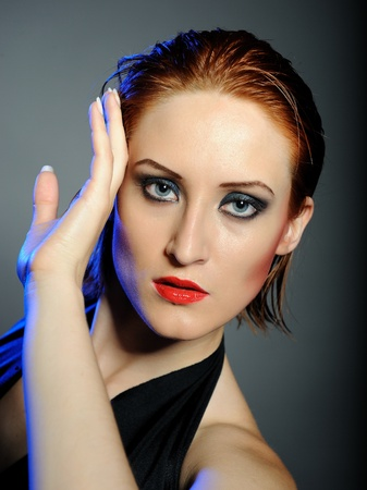 Beautiful desperate woman with perfect bright make-up with red lips and dark shadowed eyes photo