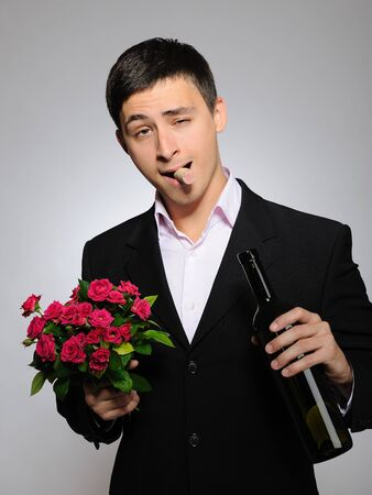 Handsome romantic young man holding rose flower and vine bottle  prepared for a date. gray background Stock Photo - 8244268