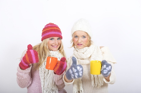 two beautiful winter woman friends in warm clothes drinking tea Stock Photo - 8328418