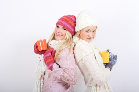 two beautiful winter woman friends in warm clothes drinking tea Stock Photo - 8328405