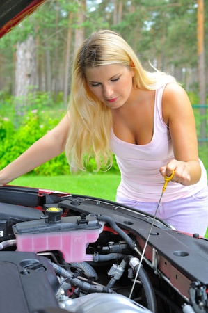 Young woman checking oil level in the car  Stock Photo