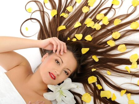 Beautiful spa woman with long healthy hair and bright make-up relaxing on the floor with yellow rose petals. isolated on white background photo