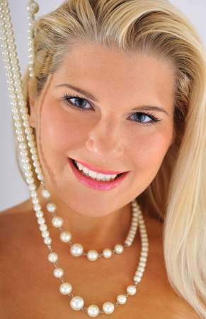 young beautiful woman with white healthy teeth and pearl necklace photo