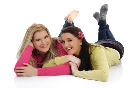 Twee mooie meisje vrienden met plezier en lachen op de vloer. geïsoleerd op witte achtergrond Stockfoto
