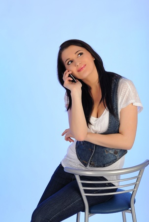 Pretty casual woman speaking on the phone sitting on the chair photo