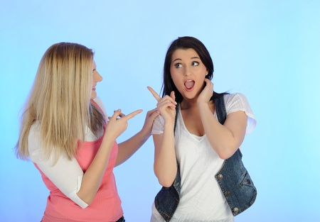 Two young pretty woman gossiping and enjoying conversation. isolated on blue background photo