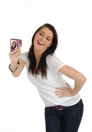 beautiful casual woman taking her own pictures on a digital photo camera. isolated on white background