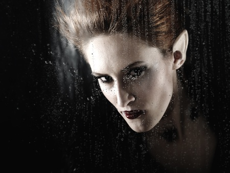 Portrait of a beautiful fashion vampire woman behind rainy window photo