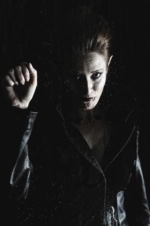 Portrait of a beautiful fashion vampire woman behind rainy window Stock Photo - 8536988
