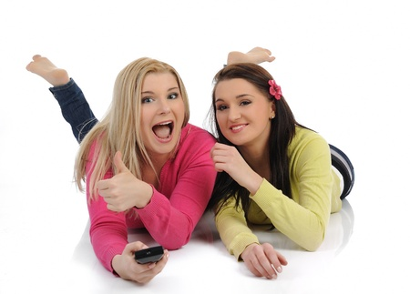 two young pretty woman friends watching television and switching channels on remote control photo
