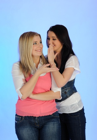 chatty: Two young pretty woman gossiping and enjoying conversation. isolated on blue background
