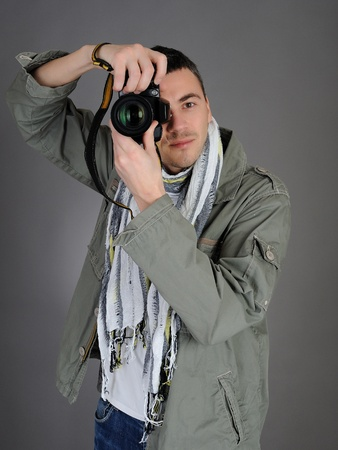 professional male photographer taking picture . isolated on gray background  Stock Photo