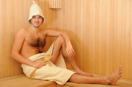 Young handsome man in a towel relaxing in a russian wooden sauna photo