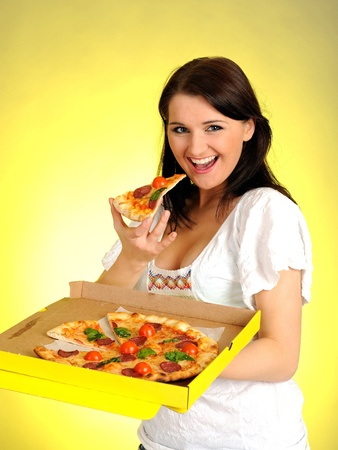 Pretty young casual brunette girl eating tasty pizza
