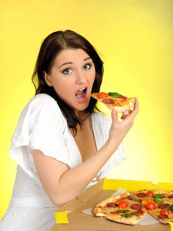 pica: Pretty young casual brunette girl eating tasty pizza