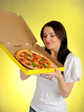 pica: Pretty young casual girl with tasty pizza in delivery paper box. isolated on white background