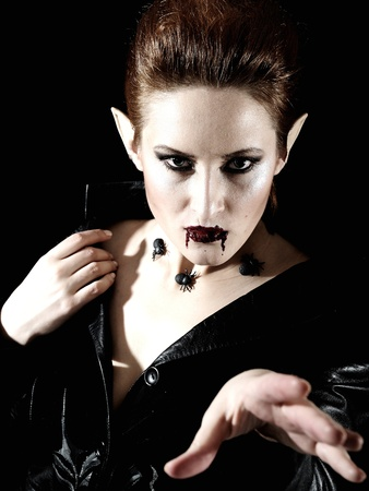 Terrible fashion vampire woman with spiders and blood photo