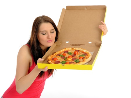 Pretty young casual woman with tasty pizza in delivery paper box. isolated on white background photo