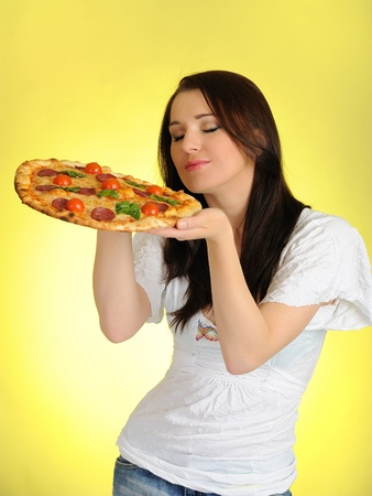 Pretty young casual girl with tasty pizza in delivery paper box. isolated on yellow background photo