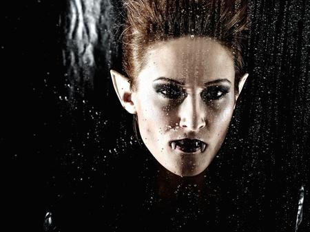 Portrait horrible fashion vampire woman behind rainy window Stock Photo - 8737783