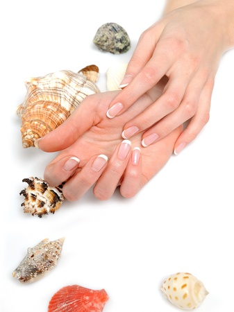 Beautiful hands with perfect spa french manicure with many sea shells. isolated on white background photo