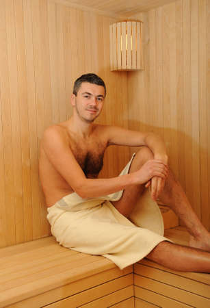 steam room: Young handsome man in a towel relaxing in a russian wooden sauna