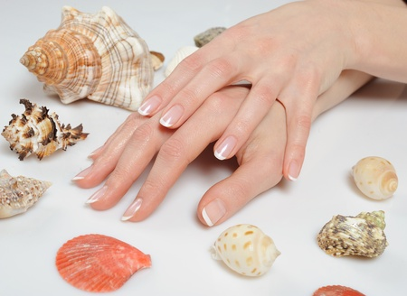 Beautiful hands with perfect spa french manicure with many sea shells.