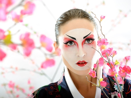 Artistic portrait of japan geisha woman with creative make-up near sakura tree photo