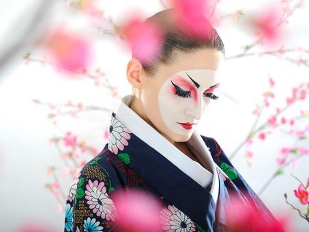 kimono: Retrato art�stico de mujer de geisha de Jap�n con maquillaje creativo cerca de �rbol de sakura