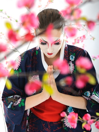 Artistic portrait of japan geisha woman with creative make-up near sakura tree in kimono