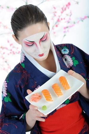 beautiful japan geisha woman with sushi roll set photo