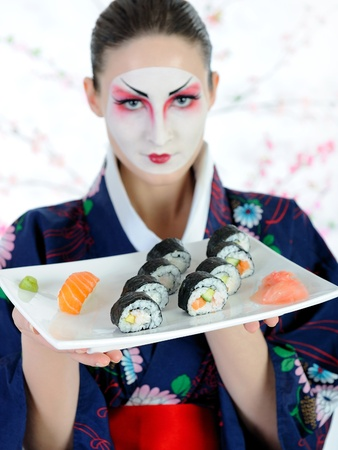 beautiful japan geisha woman with sushi roll set photo