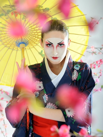 Artistic portrait of japan geisha woman with creative make-up near sakura tree in kimono with umbrella photo