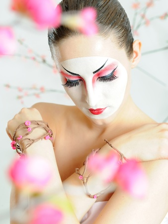 japan geisha woman with creative make-up in sakura garden.close-up artistic portrait photo