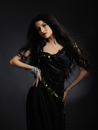 Beautiful woman with long black healthy hair in arabic traditional clothes photo